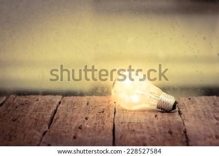 Light bulb  on wood table - stock photo