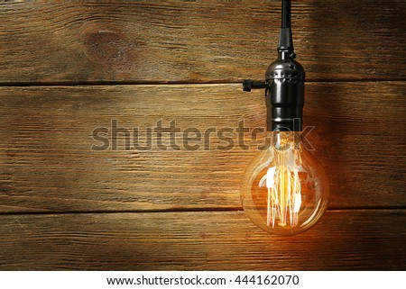 Light bulb on wooden background, close up - stock photo