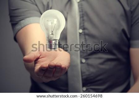 light bulb over hand - stock photo