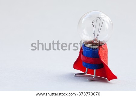 Light bulb super hero dressed in blue suit and red cape. Success man creative concept, fun, kind character. copy space, soft gray background - stock photo