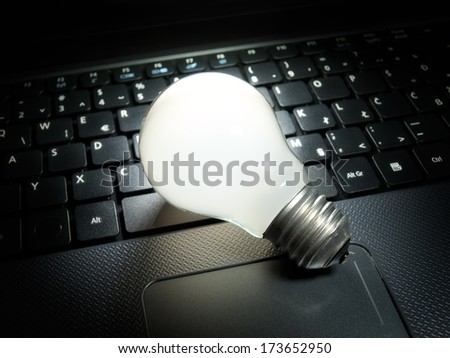 Light bulb that is lit on your computer keyboard as symbol of new ideas in computing and electronics. - stock photo