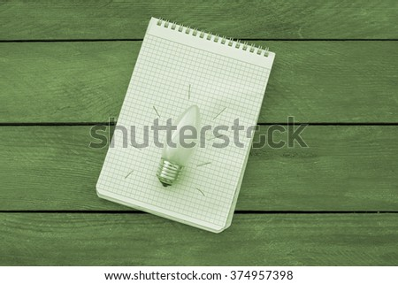 Light bulb with an idea in a notebook on a wooden table top with gray tinge - stock photo