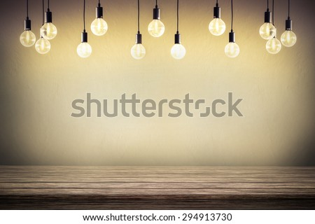 Light bulb with cement wall background,wood table - stock photo
