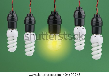 Light Bulb with Energy Saving Bulb on Green Background - stock photo