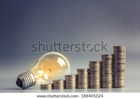 Light bulb with heap of coins stairs for financial plan or business idea concept - stock photo