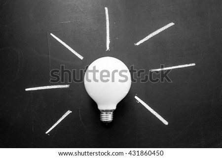 Light bulb with rays written by white chalk on the black chalkboard,  light bulb idea , business idea , business concept ,Innovation concept - stock photo