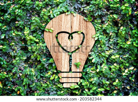 Light Bulb wood icon and heart shape inside on green leaf wall,Eco concept - stock photo