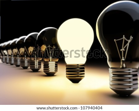 Light bulbs in a row, one being on with depth of field, part of a innovation concept - stock photo