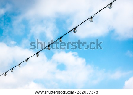 light bulbs on a wire with cloudy sky - stock photo