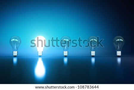 light bulbs stand in rows one glows on a blue background - stock photo