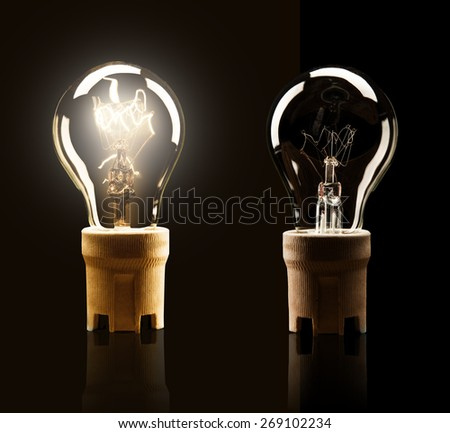 Light bulbs switched on and off, isolated on black background - stock photo