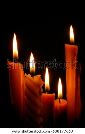 light candle burning brightly in the black background