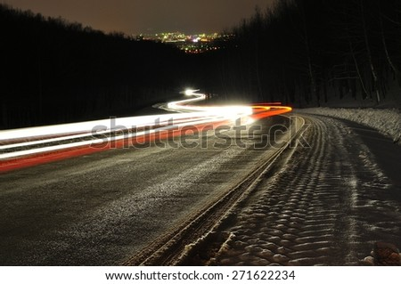 Light car headlights at night road in winter - stock photo