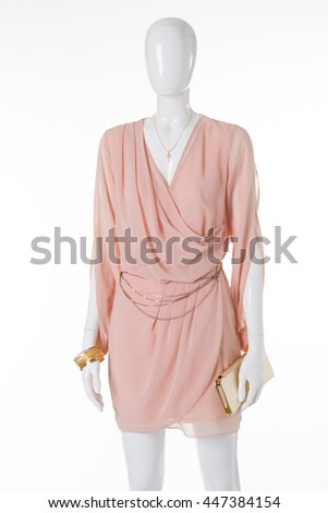 Light chiffon dress on a mannequin. Gently peach evening dress with gold accessories. - stock photo