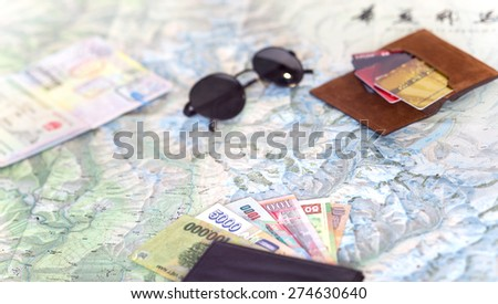 Light color composition on travel topic.  Unfolded detailed topographic map exotic Asian cash notes credit cards sunglasses passport entry stamps many - stock photo