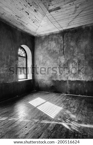 Light coming through abandoned house's window (black and white) - stock photo