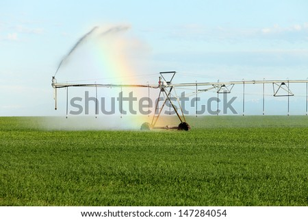Light diffracts through the spray of a center pivot sprinkler system creating a rainbow as it irrigates a farm field - stock photo