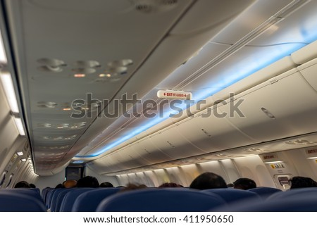 Light down on boarding; Emergency Exit Row in Airplane; Exit sign in Thai Language;  - stock photo