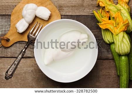light food: mozzarella with liquid inside ceramic bowl and fresh zucchini - stock photo
