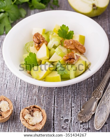 Light fresh spring salad with green apple, stem celery, walnuts in a white bowl on a simple wooden background surrounded by ingredients. selective Focus