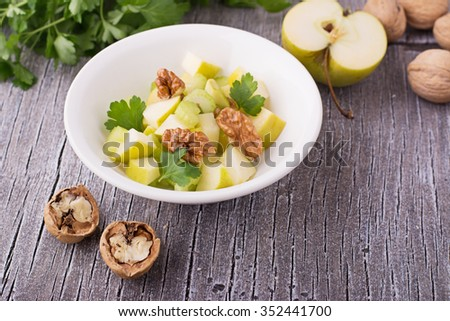 Light fresh spring salad with green apple, stem celery, walnuts in a white bowl on a simple wooden background surrounded by ingredients. selective Focus - stock photo