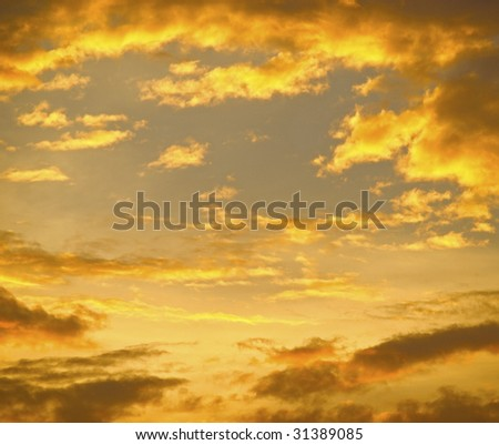Light from setting sun colored clouds in yellow. Golden clouds background.