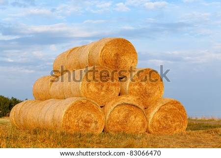 light golden haystack on the meadow over autumnal blue cloudy sky