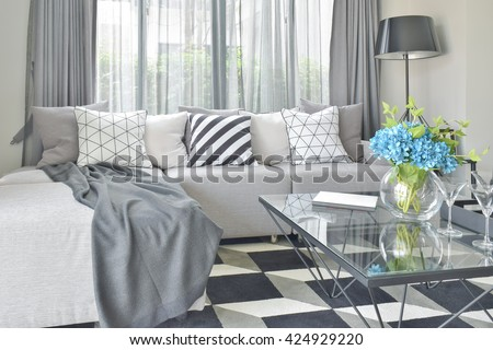 Light gray L shape sofa set with varies pattern and color pillows in modern living room - stock photo