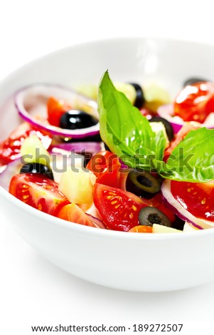 Light greek mediterranean salad with fresh vegetables, garnished with basil. Isolated on white. Selective focus. Vertical composition.