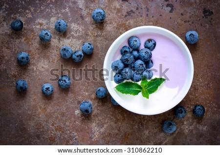 Light greek yogurt or cream dessert with fresh blueberries served in white bowl, top view, stylized photo - stock photo