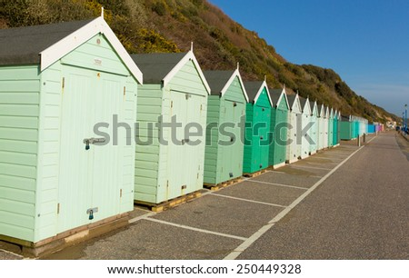 Light green beach huts in a row with blue sky traditional English structure and shelter found at the seaside - stock photo