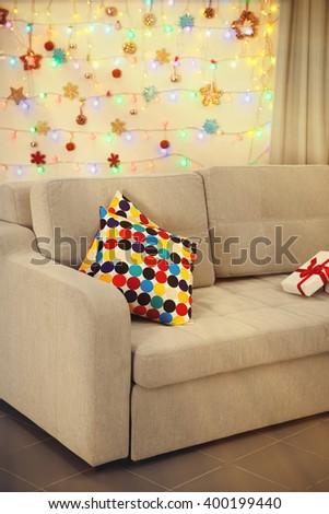 Light grey couch with pillows on Christmas lights background