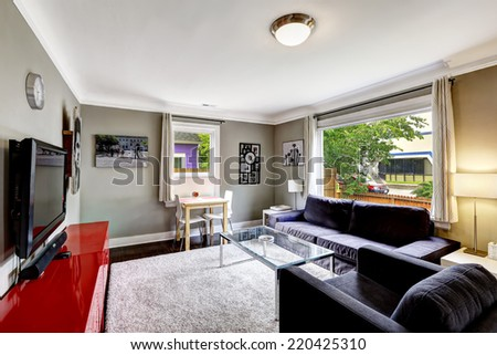 Light grey living room with bright red cabinet. Black sofa and armchair with glass top coffee table - stock photo