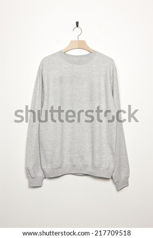 light grey long shirts with wood hanger isolated white. - stock photo