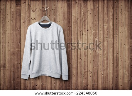 Light grey sweater on a wood wall