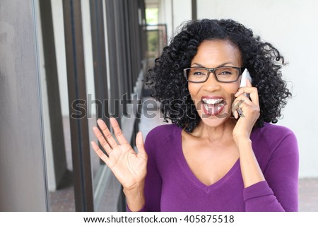 Light-hearted gossip conversation by African American gorgeous mature woman on mobile phone - stock photo
