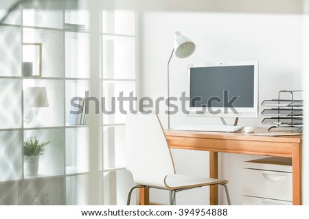 Light home office with simple chair and wood desk, standing lamp and computer
