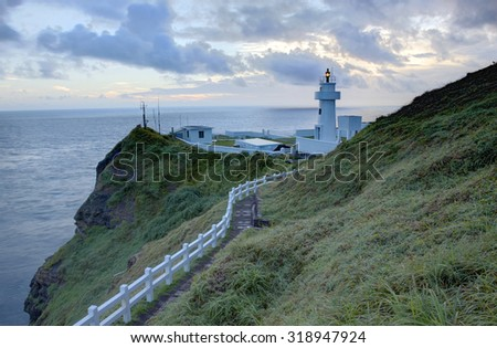 Light house~ Hiking trail leading to a lighthouse on the cliff in northern coast of Taiwan at sunrise - stock photo