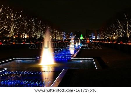Light illuminating a row of water fountains. - stock photo