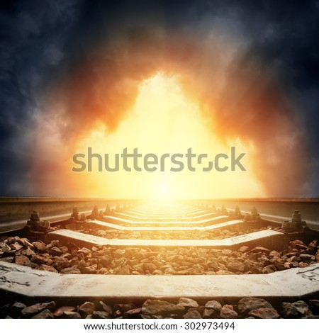 light in dramatic sky hole and railroad to horizon - stock photo