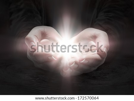light in hands - pray the crucifix in darkness  - stock photo