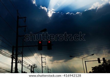 light in the dark sky with clouds, and light poles with the red arrow.