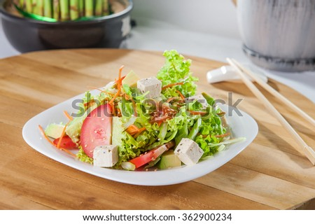 Light  japanese vegetarian salad with tofu cheese and avocado on the  white square plate on the light wood table - stock photo