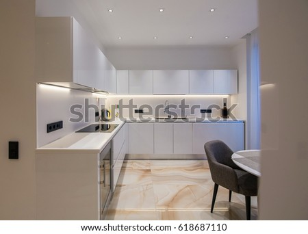 Light kitchen with marble floor, dinning room with round table and chairs, stock photo