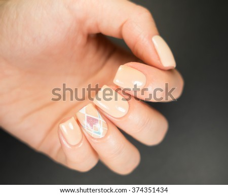 Light manicure in light on a black background.