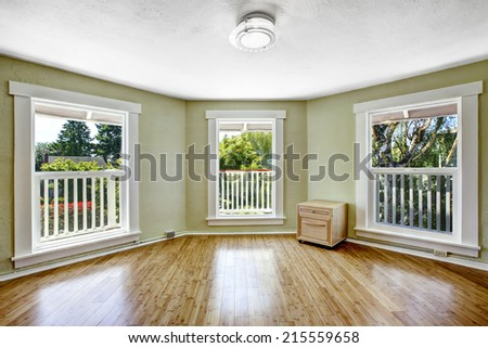 Light mint empty room with three windows and hardwood floor
