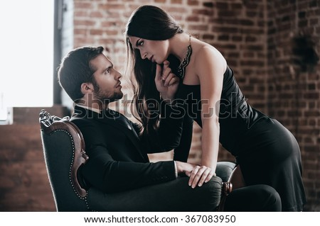 Light my fire! Beautiful young woman in cocktail dress leaning to her boyfriend sitting in chair while looking at each other in loft interior - stock photo