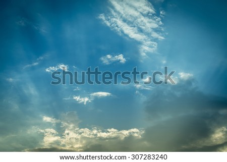 light of sunbeam on blue sky background with clouds - stock photo