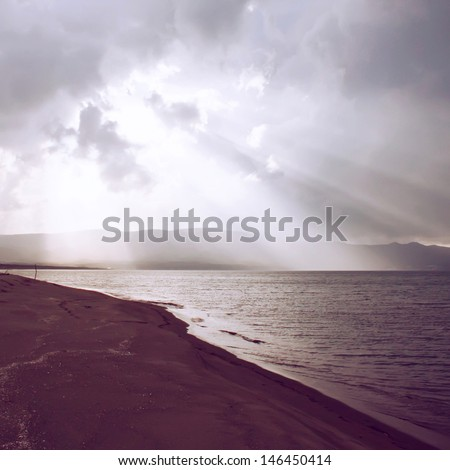 Light of sunbeam through clouds to the sea with retro filter effect   - stock photo
