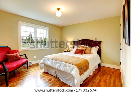Light olive bedroom with hardwood floor and white french window. Furnished with a bed and an antique red settee - stock photo